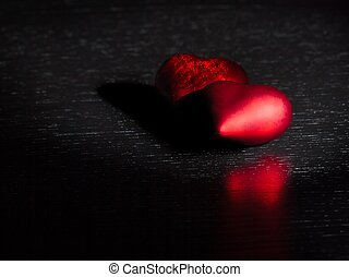 two decorative red hearts on black dark light and on wood...
