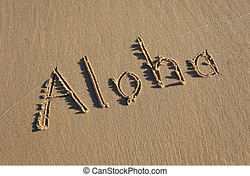 Aloha written in the sand at the beach. Aloha is a famous...