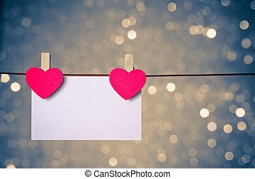 two decorative red hearts with greeting card hanging on blue...