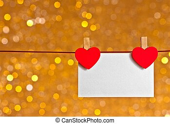 two decorative red hearts with greeting card hanging on...