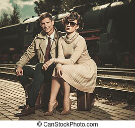 Beautiful vintage style couple sitting on suitcases on train...