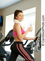 Young woman doing exercise in fitness club on training machine