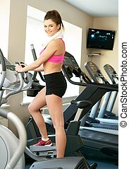 Young woman doing exercise in fitness club on training...