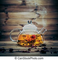 Glass teapot with blooming tea flower inside against wooden...
