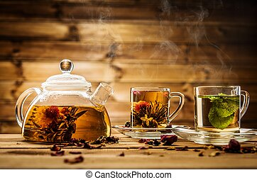 Teapot and glass cups with  tea against wooden background