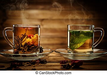 lass cups with tea against wooden background - Two glass...