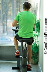 Man doing exercise on a bike in a fitness club