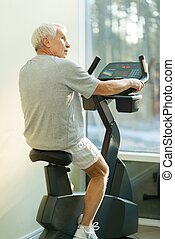 Senior man doing exercise on a bike in a fitness club