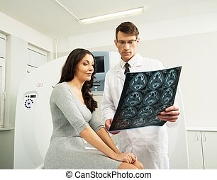 Doctor with young woman patient looking at the computed...