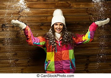 Smiling woman in ski jacket and white hat standing against...
