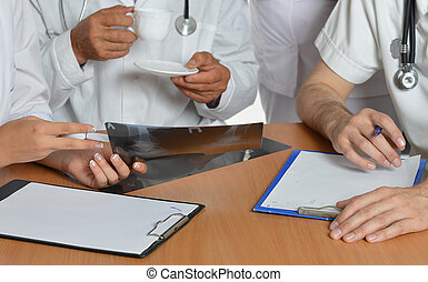 Closeup of doctors hands having a discussion at table