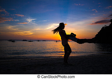 Little girl and her mother having fun at sunset on the island Boracay, Philippines