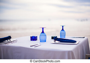 Summer empty open air table set for dinner on white beach