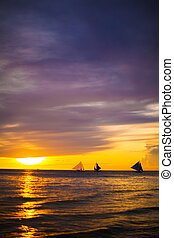 Colorful beautiful sunset with sailboat on the horizon in...