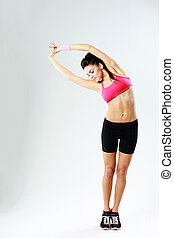Young beautiful sport woman stretching on gray background
