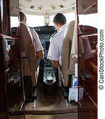 Pilot And Copilot Operating Private Jet - Rear view of pilot...