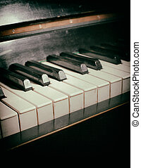 Old piano keyboard close up as a music background. With dust...