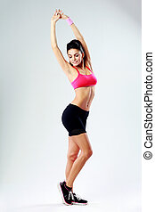 Young happy sport woman stretching on gray background