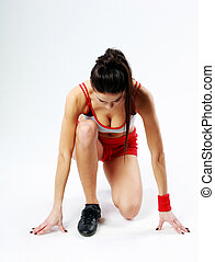 Young sexy fitness woman start running on gray background