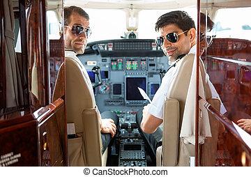Confident Pilots In Cockpit Of Plane - Portrait of confident...
