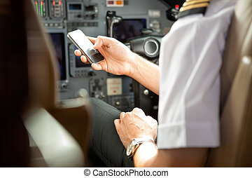 Pilot Using Cell Phone In Cockpit - Cropped image of pilot...