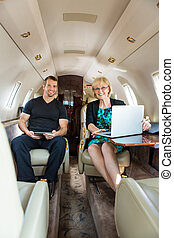Confident Business People In Corporate Jet - Portrait of...