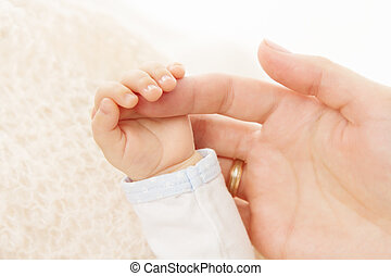 Newborn baby hand holding parent finger