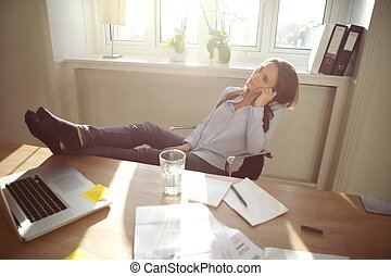 Relaxed businesswoman with legs on the desk - Young business...