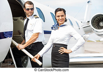 Pilot and Stewardess on Private Jet - Portrait of beautiful...