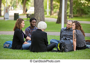 Multiethnic Friends Relaxing On Grass At Campus