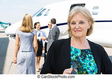 Portrait Of Confident Businesswoman Against Private Jet -...