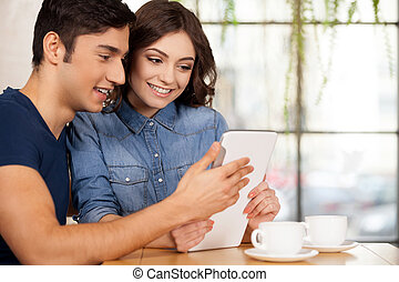 Surfing the net together. Beautiful young couple sitting...