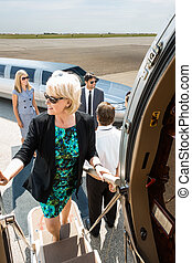 Mature Businesswoman Boarding Private Jet - Mature...