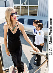 Rich Woman Boarding Private Jet - Full length of rich woman...