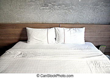 White bed with a pillow or two.