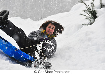 Sledding on a saucer - Teenage girl sledding in the snow on...