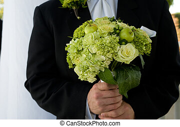 Groom holding bouquet - Groom holding a bouquet of green...