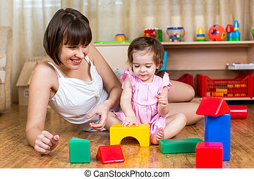 mother and kid play with building block toys at home