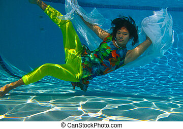 Teenage girl swimming with veil - Teen girl in bright...