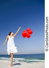 Jumping with red ballons - Beautiful girl jumping with red...