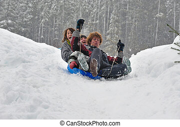 Teens sledding on a saucer - Teenagers sledding in the snow...