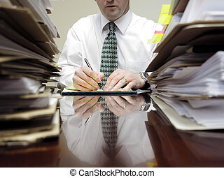 Businessman at Desk with Piles of Files - Businessman...
