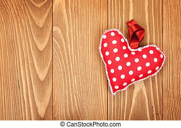 Red Valentine's day heart toy. On wooden background with...