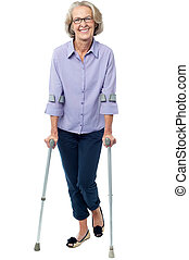 Old woman walking with crutches