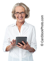 Aged woman using touch pad device - Senior citizen posing...