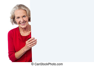 Aged woman holding blank ad board - Smiling aged woman with...