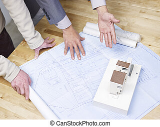 reviewing the blueprint - businessman pointing at an...