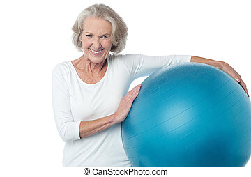 Senior woman posing with exercise ball - Fit aged woman...