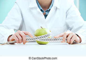 Diet concept - Young female doctor holding measuring tape...