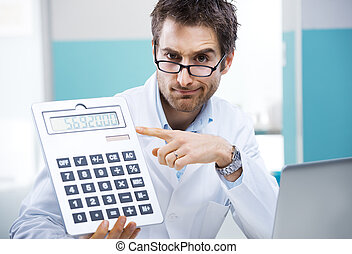 Doctor and calculator - Young friendly doctor pointing at a...
